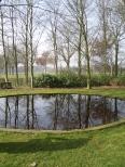 Die laublosen Bäume spiegeln sich im schnörkellosen Teich und bilden dadurch eine Einheit. Garten Rosenhaege, Niederlande