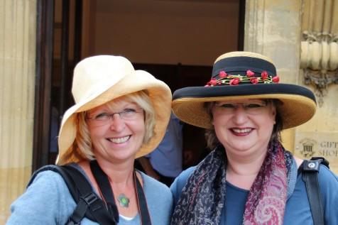 Carmen mit einem Hut aus Papierstroh und Martina trägt einen edlen breitkrempigen Hut, dessen Borte mit zahlreichen Röschen verziert ist.